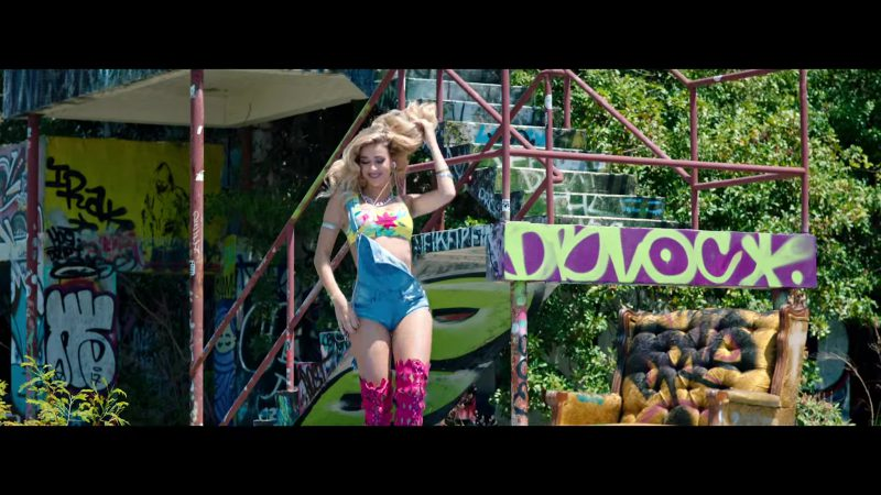 "Printed Yellow Crop Top and Denim Overall Shorts Worn by Model in ""Única"" by Ozuna Music Video"