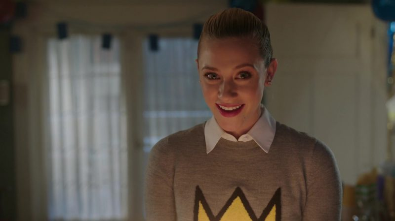 """Fashion Trends 2021: Grey Sweater With Yellow Crown Logo Worn by Lili Reinhart in """"Riverdale"""""""